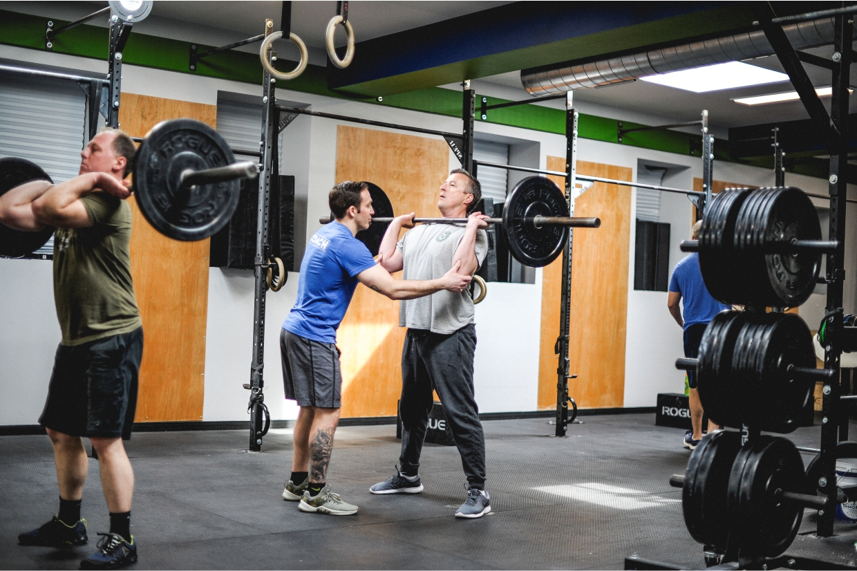 personal trainer helping a man lift a barbell immortal fitness personal training