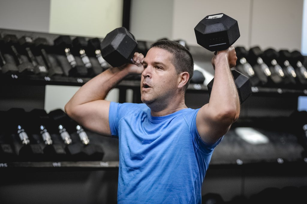 man holding dumbbells new to immortal fitness gym