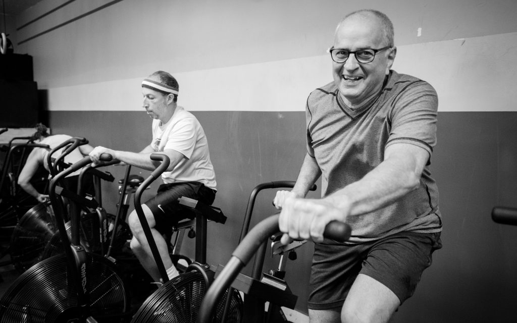 man smiling while on a workout bike new to immortal fitness gym