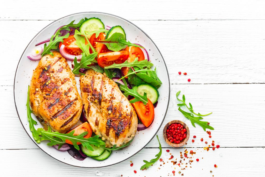 Grilled chicken breast. Fried chicken fillet and fresh vegetable salad of tomatoes, cucumbers and arugula leaves. Chicken meat salad. Healthy food. Flat lay. Top view. White background immortal fitness gym pleasantville ny